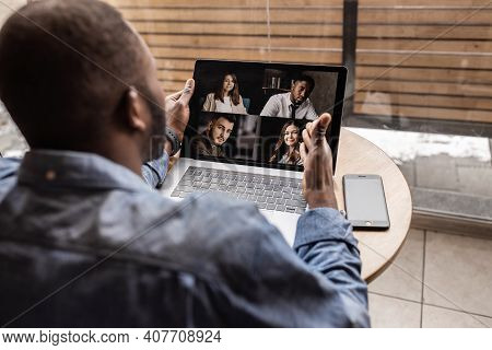 Back View. African-american Worker Discusses Brainstorming Video Call With Various Colleagues, Scree