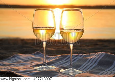 Glasses Of Delicious Wine On Riverside At Sunset