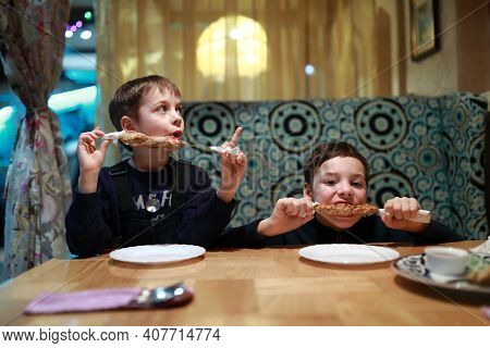 Boys Eating Kebab On Skewers In Restaurant