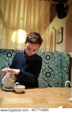 Portrait Of Kid Pouring Tea In Restaurant