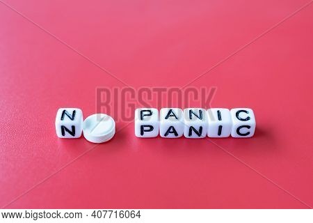 The Inscription No Panic Instead Of The Letter O Round White Tablet, Cubes On A Red Background