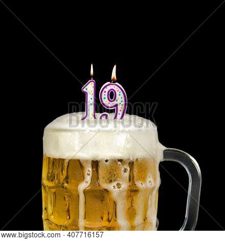 Number 19 Candle In Beer Mug For Birthday Celebration Isolated On Black