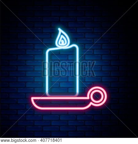 Glowing Neon Line Burning Candle In Candlestick Icon Isolated On Brick Wall Background. Old Fashione