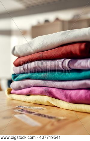 Custom Apparel, Clothes Neatly Folded On Shelves. Stack Of Colorful Clothing In The Store. Vertical