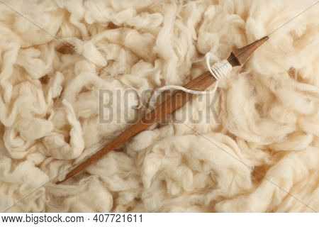 Soft White Wool With Spindle As Background, Top View