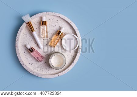 Skin Care Essence Glass Bottles And Jar With Facial Cream On Marble Cosmetic Tray On Blue Background