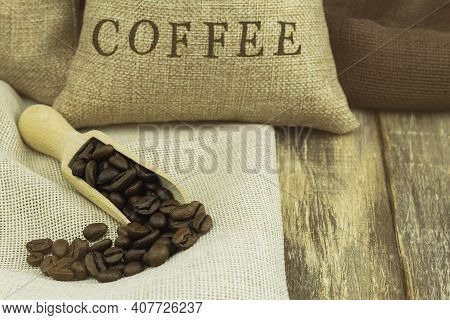 Coffee Beans In A Wooden Scoop On A Wooden Background With Space For Text. Coffee Bean On Wooden Spo