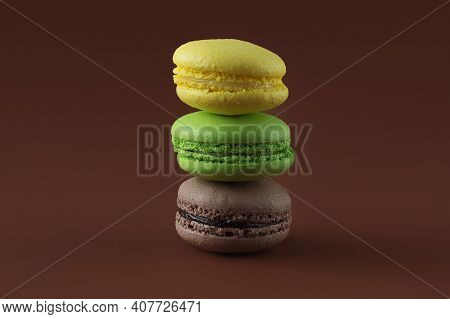 Three Delicious Fresh French Macarons On A Brown Background. A Stack Of Chocolate, Apple And Lemon B