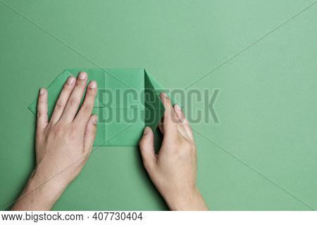 Young Hands Folding A Green Piece Of Paper To Make An Origami Four-leaf Clover, On A Green Backgroun