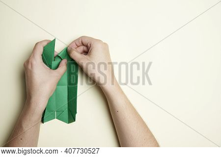 Creation Process Of An Origami Clover: Young Hands Folding A Green Piece Of Paper, On A Light Cream