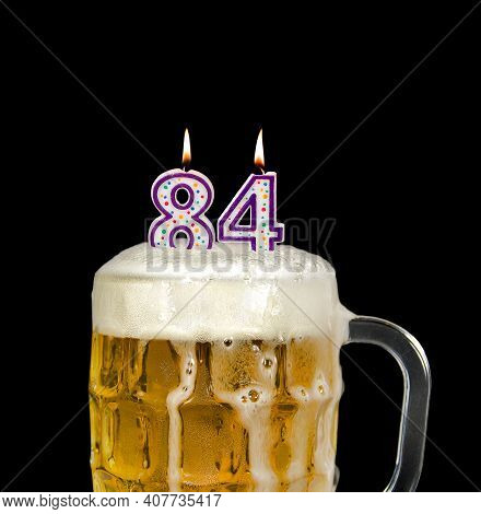 Number 84 Candle In Beer Mug For Birthday Celebration Isolated On Black