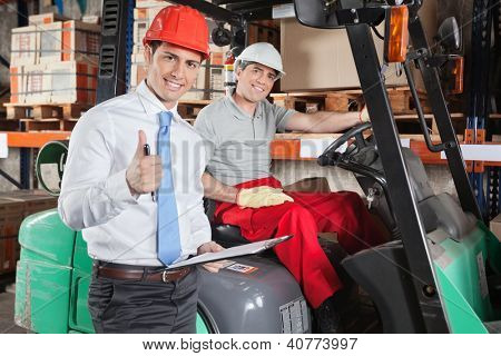 Portrait of supervisor gesturing thumbs up with forklift driver sitting behind