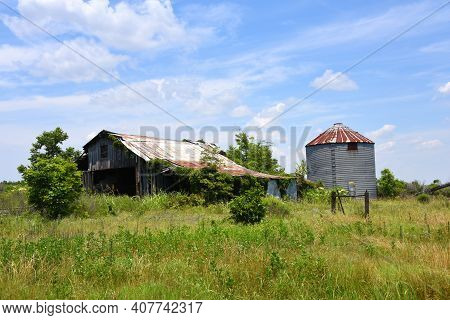 Weathered And Broken, Wooden Barn Is Overgrown With Weeds And Vines.  Rusty, Silo Stands Behind Barn