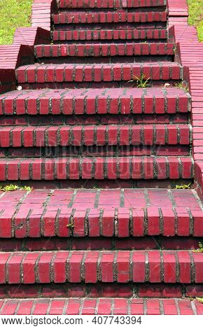 Steep, Red, Brick Steps Ascend And Descend.  Rustic With Sprigs Of Grass Growing From Cracks.
