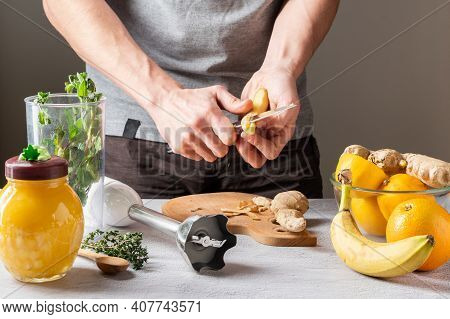 Peel Ginger Root From The Shell. Clean Food In The Kitchen. Kitchen Knife In Hand. Peel The Skin Wit