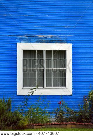 Rustic, Wooden House Is Painted Blue.  Window Is Trimmed In White.  Flowers And Landscaping At Botto