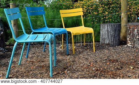 Colorful Metal Chairs Sit In A Row In Memphis Riverfront Park In Memphis, Tennessee.  Tree Stumps Ar