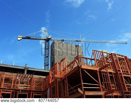 Tall Crane Stands Above A Construction Site In Memphis, Tennessee.  Wooden Framing Stands Open Ready