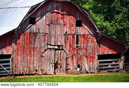 Closeup Of The Front Of This Old, Red Wooden Barn, Shows Broken And Missing Boards.  Exterior Has Be