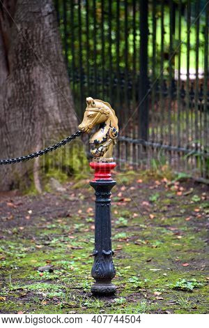 Hitching Horse Decorates Yard.  It Is Painted Gold With Red And Black Base.  It Sits Outdoors With B