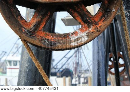 Partial View Of A Large Rusty Pulley Wheel Of A Deep Sea Fishing Boat In Port.