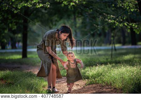 The Baby Girl Takes The First Steps, A Young Mother Holding A Child By The Hands, Insuring, Helping
