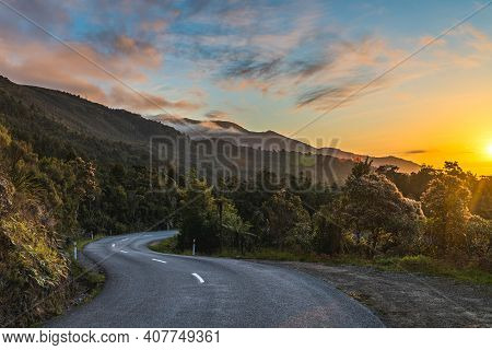 Winding Mountain Road Leading To The Ocean During Sunset. Deep Yellow And Blue Tones.