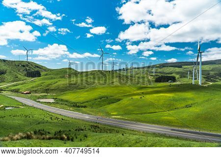 Wind Farm With Multiple Turbines Along A Winding Country Road. Set In A Meadow With A Farmland Feel