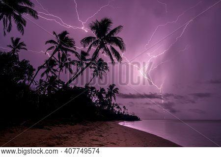 Landscape Shot Of Purple Chain Lightning Illuminating A Sandy Palm Beach With Golden Sand