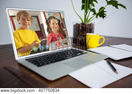Caucasian schoolboy and schoolgirl learning displayed on laptop screen during video call. Online education staying at home in self isolation during quarantine lockdown.