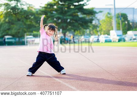 Active Girl Exercising In Sports Field. Happy Child Smiled Sweetly And Laughed Happily. Children Pla