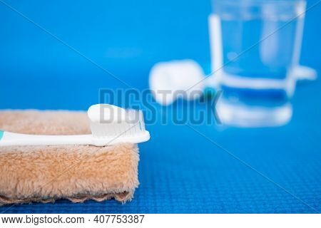 Toothpaste On Toothbrush And Brown Towel With Toothpaste And Water Glass Blerred On Blue Background.