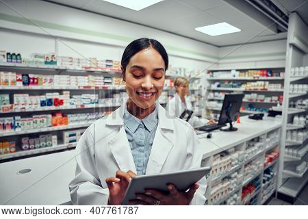 Successful Young Female Pharmacist Using Digital Tablet In Drugstore With Colleague Using Computer I