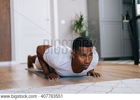 Close-up View Of Focused African-american Man Doing Push-up On Floor At Cozy Domestic Room, Looking