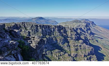 Mountain Panorama From The Summit Of Table Mountain In Cape Town. Rocky Slopes And Peaks With Little
