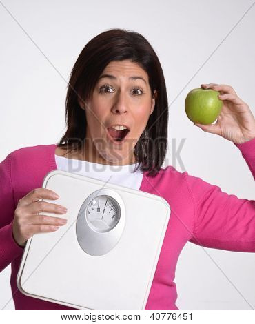Happy slim and diet fat woman holding a weight scale and green apple.