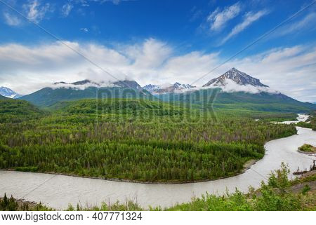 Picturesque Mountains of Alaska in summer. Snow covered massifs, glaciers and rocky peaks. Beautiful natural background.