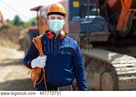 Portrait of masked worker in a construction site, covid coronavirus construction concept