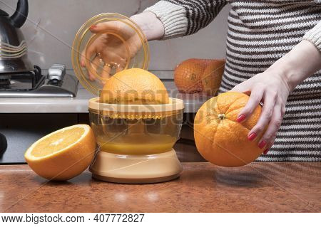 Female Hand Squeezing Orange Juice. Closeup On Women's Hand Making Fresh Orange Juice. Juicing Orang