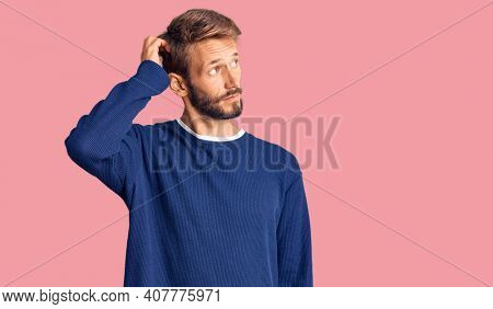 Handsome blond man with beard wearing casual sweater confuse and wondering about question. uncertain with doubt, thinking with hand on head. pensive concept.