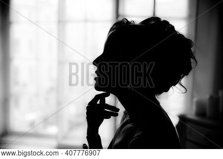Silhouette of a woman's profile on a background of a window.