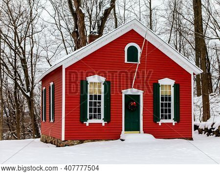 NEW CANAAN, CT, USA -FEBRUARY 9, 2021:  The Little red schoolhouse c.1865 after snow blizzard