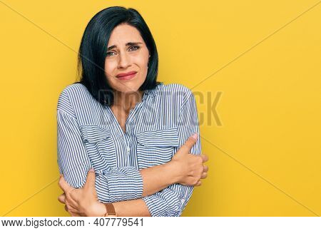 Young caucasian woman wearing casual clothes shaking and freezing for winter cold with sad and shock expression on face