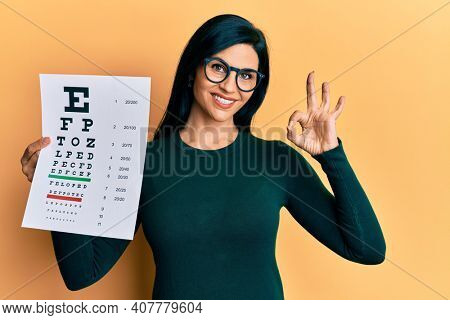 Young caucasian woman holding optometry glasses and eyesight test doing ok sign with fingers, smiling friendly gesturing excellent symbol