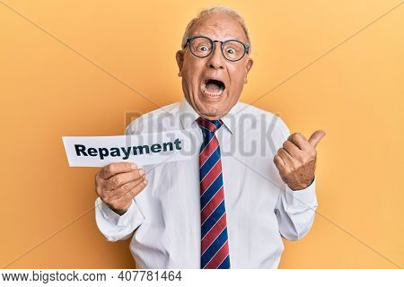 Senior caucasian man holding repayment word paper pointing thumb up to the side smiling happy with open mouth