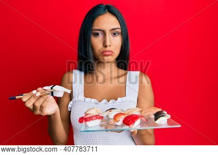 Young brunette woman eating butterfish sushi using chopsticks depressed and worry for distress, crying angry and afraid. sad expression.