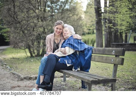 grandson with grandmother huddled in a park