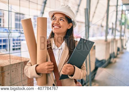 Young latin architect girl smiling happy holding blueprints standing at the city.