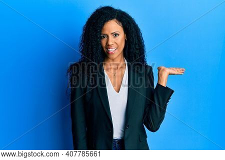 Middle age african american woman wearing business clothes smiling cheerful presenting and pointing with palm of hand looking at the camera.