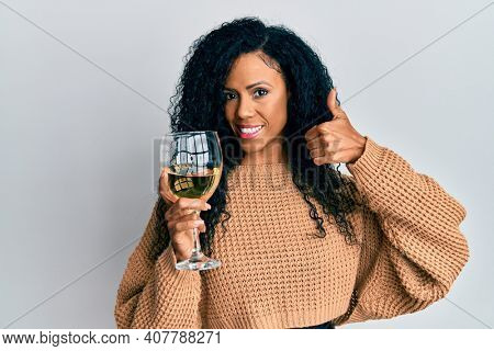 Middle age african american woman drinking a glass of white wine smiling happy and positive, thumb up doing excellent and approval sign
